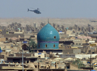 U.S. ARMY HELICOPTER FLIES OVER THE ANCIENT CEMETERY IN NAJAF.