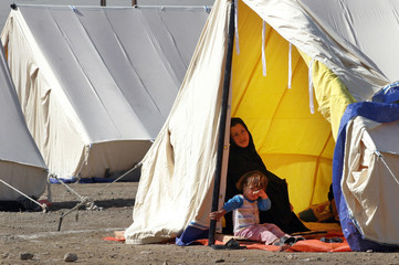 Woman and child sit in tent at newly erected refugee camp in western Iraqi town of Falluja
