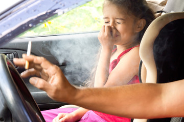 Stop smoking for children. Father smoking cigarette and the child choking of smoke in a car