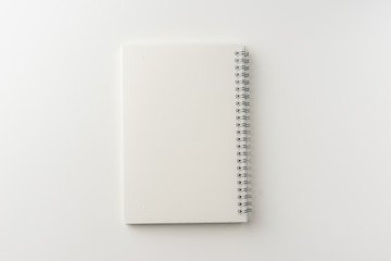 Business concept - Top view of spiral blank notebook on white background desk for mockup