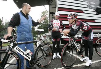 CSC team riders Cancellara and O'Grady speak with a team mechanic as they train ahead of the 94th Tour de France cycling race in London