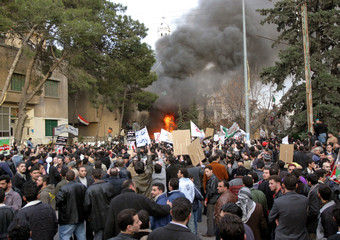 People participate in a protest outside the burning Danish embassy in Damascus