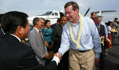 The US Health Secretary Leavitt greets Cambodian health officials upon his arrival at Phnom Penh international airport