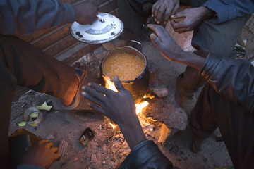 A group of would-be immigrants cook outside an abandoned farm in Nijar