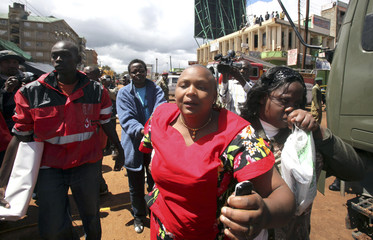 Woman mourn their relatives who were killed when a building under construction collapsed in Kiambu town
