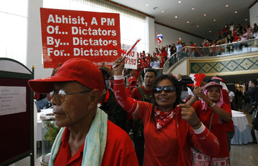 Red-shirted supporters of ousted Thai prime minister Thaksin Shinawatra enter one of the venues of the 14th ASEAN Summit and Related Summits in Pattaya