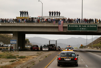 PEOPLE LINE OVERPASS TO WATCH MOTORCADE CARRYING FORMER PRESIDENT REAGAN.