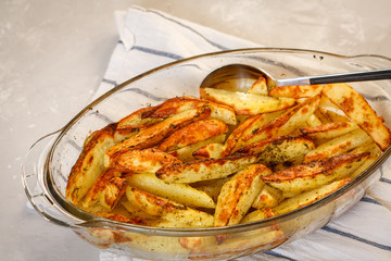 Homemade baked potatoes with spices in a glass form.