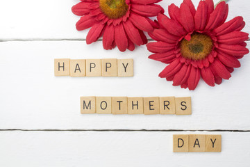 Happy mothers-day white wood background with red chrysanthemum flowers close up - top view photograph with words spelling Happy Mothers Day on wood scrabble word game pieces