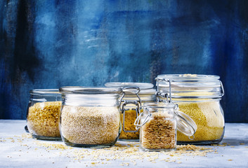 Assorted cereals in glass jars: kinoa, bulgur, couscous, orzo, brown rice, selective focus