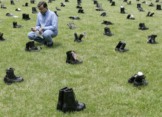 """Inayat Khan, of Indiana, looks at a pair of boots belonging to his cousin Captain Humayun Khan, which are part of """"Eyes Wide Open: An Exhibition on the Human Cost of the Iraq War""""  in Chicago"""
