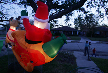 A Santa Claus blow-up doll stands in front of a house as a family walks along a street in the Lakeview area of New Orleans