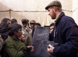 BRITISH RED CROSS WORKER JEREMY CURRIE DISTRIBUTES BLANKETS ATSHIBERGHAN PRISON.