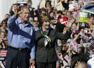 U.S. President George W. Bush and Laura Bush wave as they arrive at an election rally in Waterloo.
