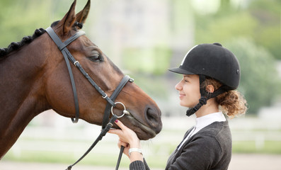 Attractive Young Woman Looking at her Horse