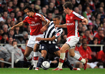 Arsenal's Barazite and Ramsey tackle West Bromwich Albion's Thomas during their English Carling Cup soccer match at the Emirates stadium in London