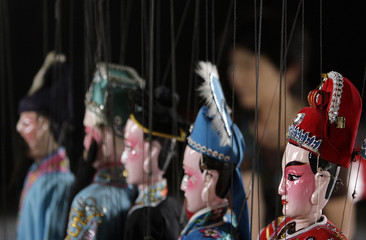 Puppets hang backstage before a traditional Chinese puppet show in a temple in Singapore March 20