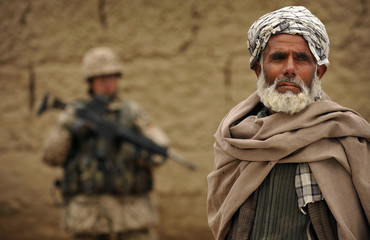 An Afghan man is seen next to a German armed forces Bundeswehr soldier during a patrol in a village in Kunduz province