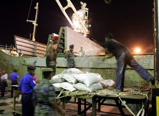 Soldiers look on as workers load a cargo ship with food and medicine at the Colombo port