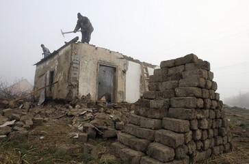 Workers demolish a farm house in the eastern Hungarian village of Alattyan