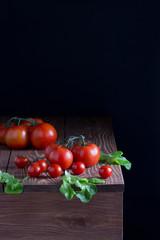 Свежие помидоры,листья салата на деревянном столе