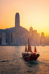 Hong kong traditional wooden chinese boat for tourist service in victoria harbor at sunset view from Kowloon side at Hong Kong