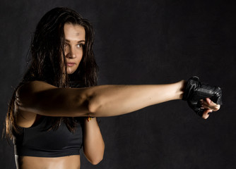 beautiful sexy female boxer or mma fighter wearing black gloves on a dark background