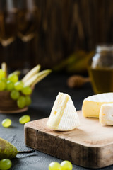 French soft cheese from Normandy region sliced with green grapes, pear, honey and glasses of wine on a wooden board on dark rustic background