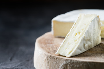 Closeup of soft cheese brie sliced on wooden cut on dark rustic background