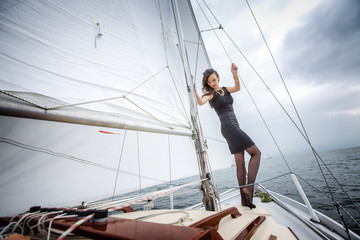 Portrait of a young cute brunette girl in a black dress posing on a yacht in the sea