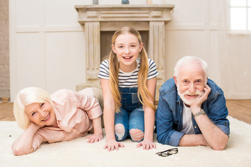 Happy little girl with smiling grandpa and grandma resting together at home