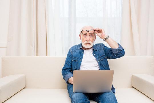 Shocked senior man sitting with laptop on knees and holding eyeglasses