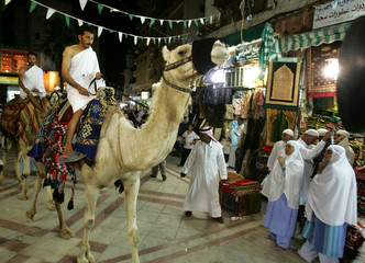 Muslim pilgrims ride camels through a bazaar in the old city of Jeddah