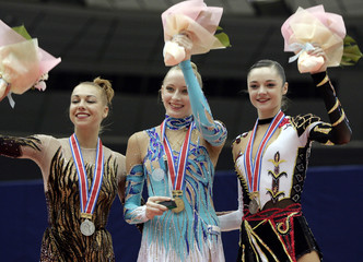 Sessina of Russia, Godunko of Ukraine and her compatriot Bessova wave after individual ribbon competition at 6th Rhythmic Gymnastics World Cup Final in Ise