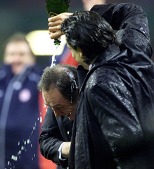 LIVERPOOL'S MANAGER HOULLIER IS SOAKED WITH CHAMPAGNE AFTER WINNING THE WORTHINGTON CUP.