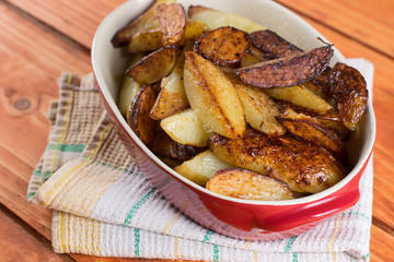 Fried young potatoes in the glass bowl over wooden background