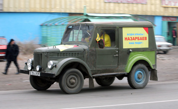 A vintage car sporting a poster supporting Kazakh President Nursultan Nazarbayev's re-election drives in the village of Shamalgan