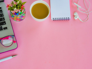 Flat lay, top view office table desk frame. feminine desk workspace with office accessories including laptop, note book, white pen, coffee cup, pink glasses,earphone and flower on pink background.