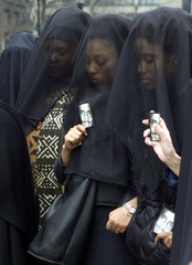 Women in black veils hold photographs of Guinean immigrant Amadou Diallo at a protest across the str..