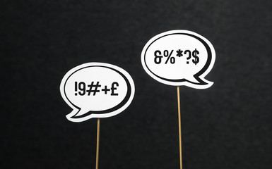 Argument, fight, curse or swearing concept. Disagreement on an online forum or internet. Two speech bubbles argue.. Speech balloon cut from paper of cardboard with wooden stick on a dark background.