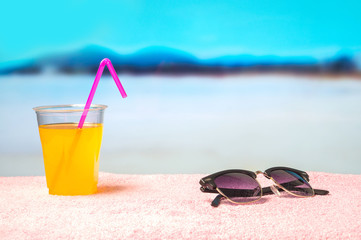 Summer background with yellow cocktail and sunglasses on towel on the beach. Beautiful blurred paradise ocean view in the background. Perfect holiday feel. Great backdrop for design, text and content.
