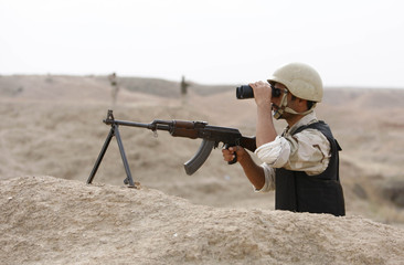 An Iraqi soldier scans his site using a pair of binoculars as he takes a postion inside one of Fakka wells near Amara