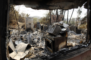 A view through a window shows the interior of a home destroyed by wildfires in the Ramona area of San Diego County