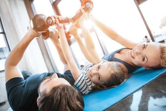 Happy family exercising with dumbbells at fitness studio,  dumbbells in heart shape