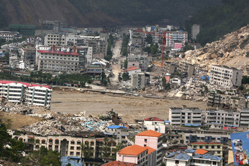 "Rushing water from a ""quake lake"" flows through the earthquake-devastated city of Beichuan"