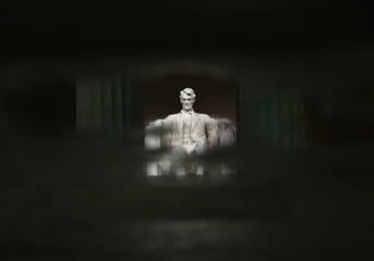 A statue of Abraham Lincoln is reflected in a puddle on the 200th anniversary of Lincoln's birth in Washington