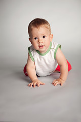 Funny kid looks closely, crawling on all fours on a gray background in the studio
