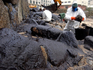 VOLUNTEERS CLEAN FUEL OIL FROM ROCKS IN MUXIA'S BEACH.