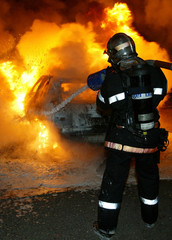 A fireman extinguishes a burning car torched during New Year's celebrations in Strasbourg's western ..