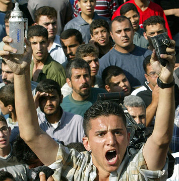 AN ANGRY PALESTINIAN YOUTH HOLDS UP A BABY'S BOTTLE AND SHOE TAKEN FROMA DESTROYED CAR IN GAZA.